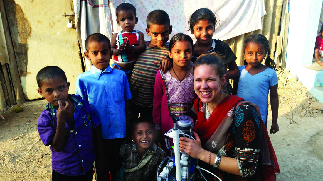 Image of student Kaylea Brase and children in Bangalore. She is holding the water filtration device she developed.