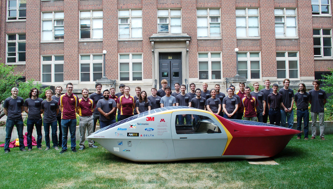 Photo of students standing with the solar-electric car