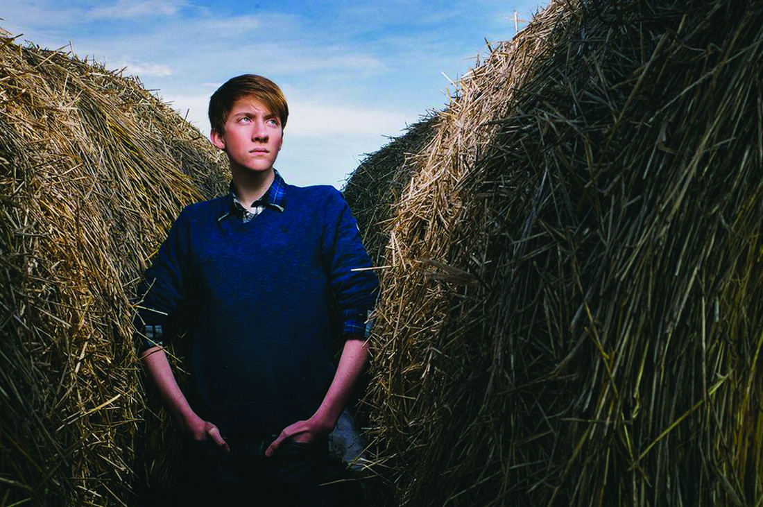 U of M student Justin Oakland standing in a hay field