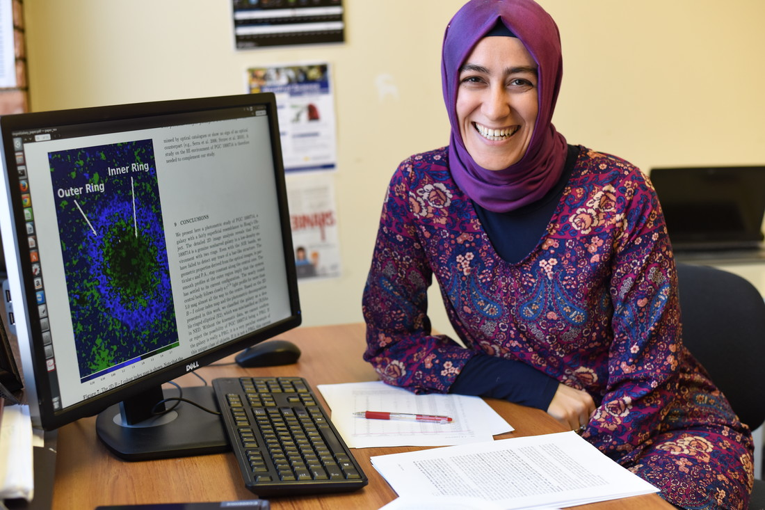Burcin Mutlu-Pakdil, a U of M graduate student and UMD teaching assistant, next to a computer screen showing an image of the galaxy she discovered.