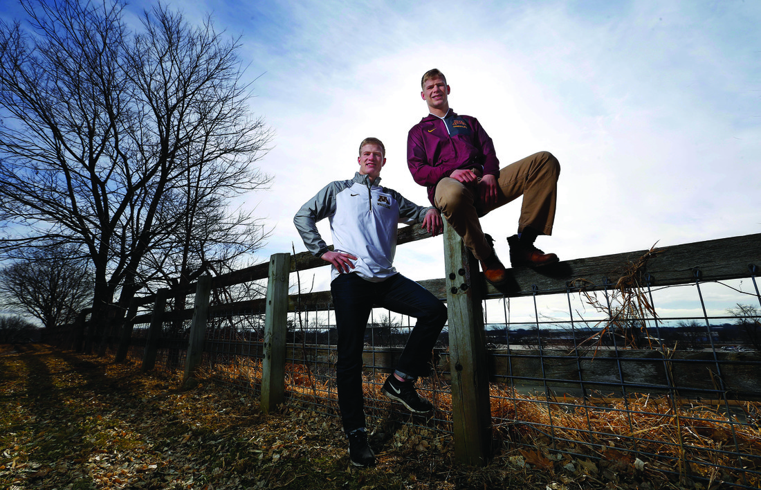 Brett and Chris Pfarr next to a fence on the family farm