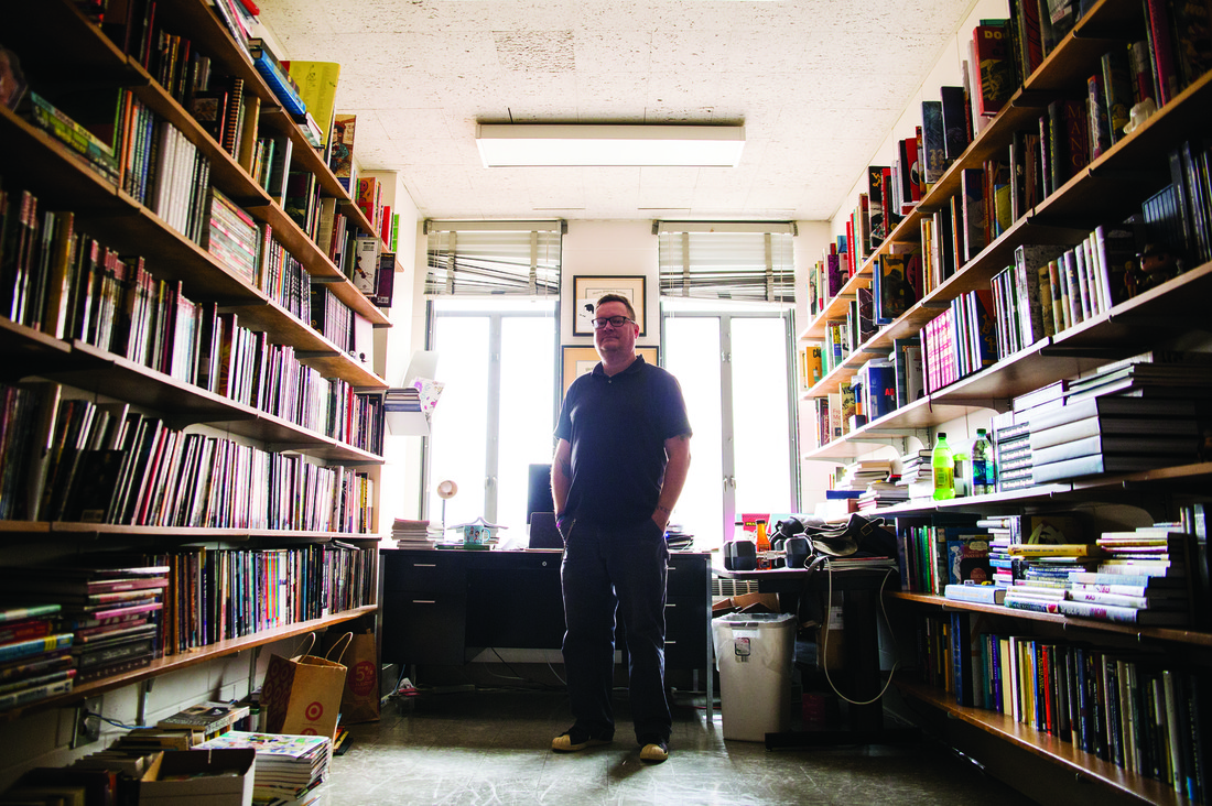 Roy T. Cook standing in his office surrounded by shelves of books.