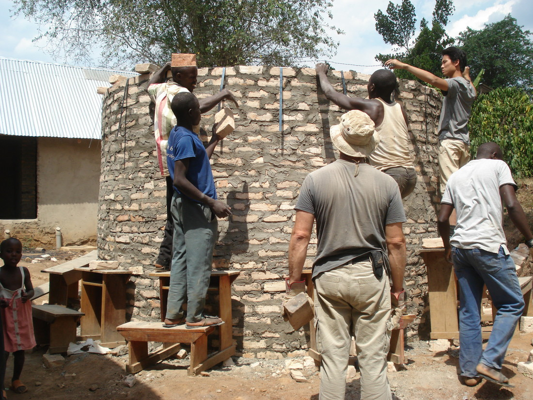 Photo of students and residents of Kyetume, Uganda, building a rainwater storage tank