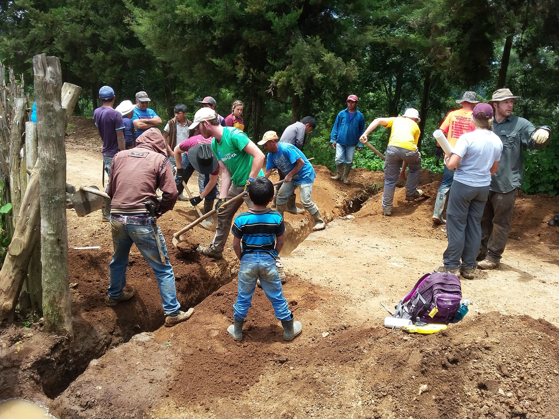 Photo of students and residents of Xiquin Sanahi, Guatemala, installing water distribution pipelines