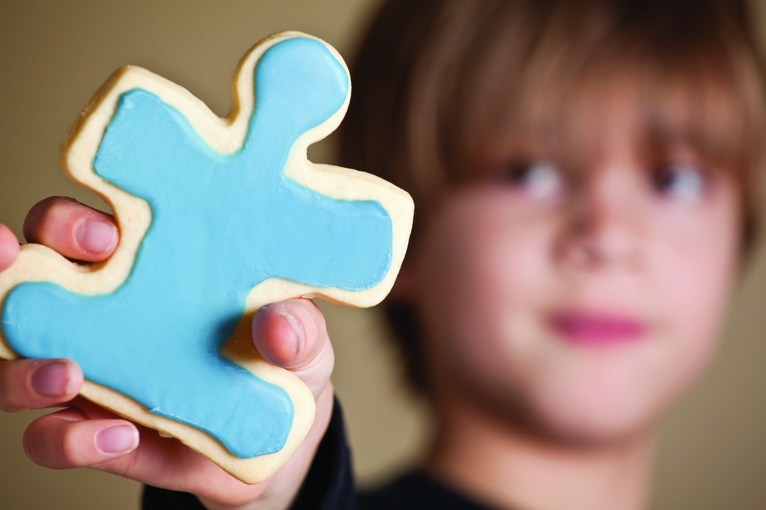 Boy holding blue frosted cookie that's shaped like a puzzle piece