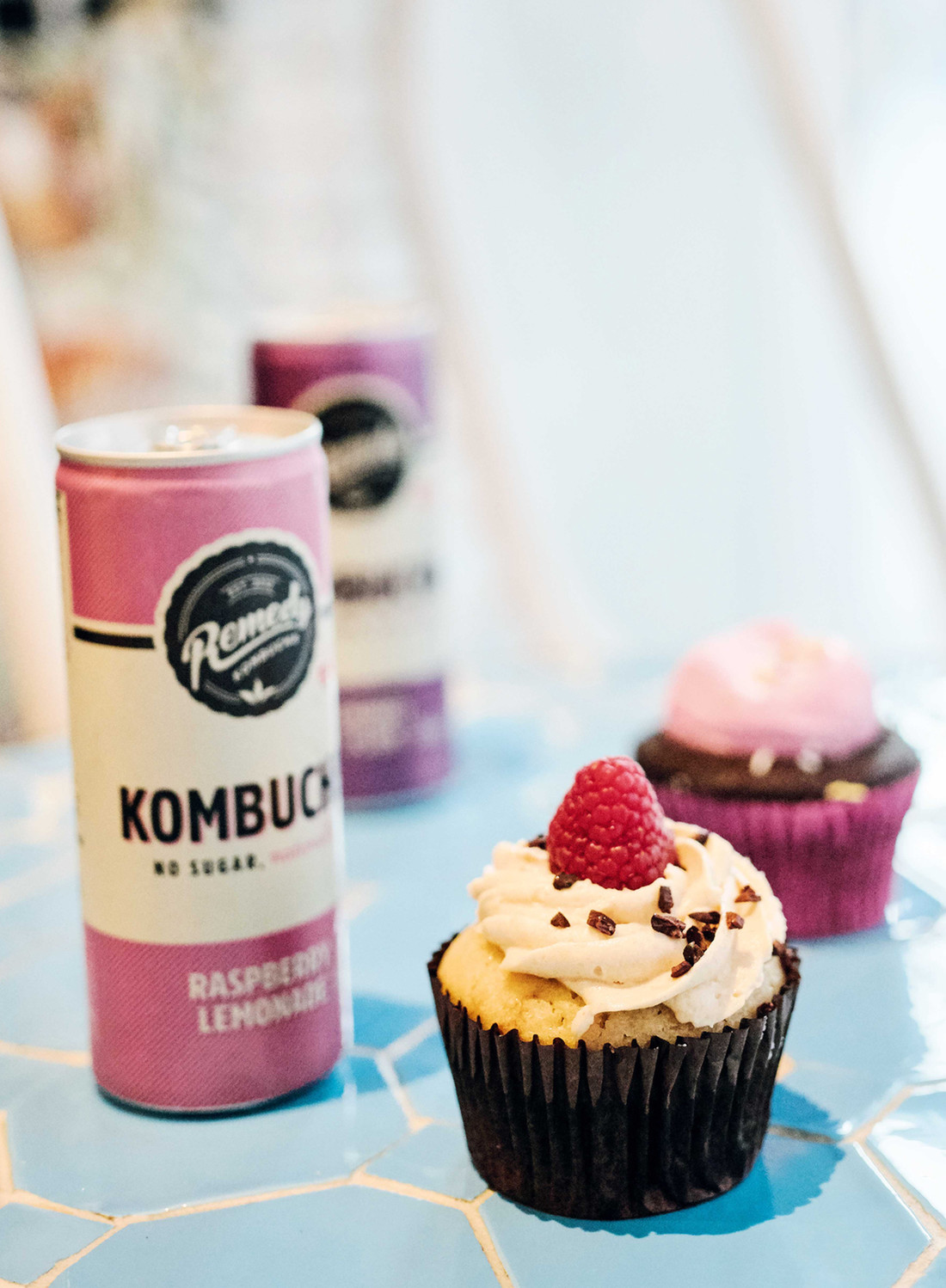 Cupcake with raspberry on top served with kombucha at by CHLOE